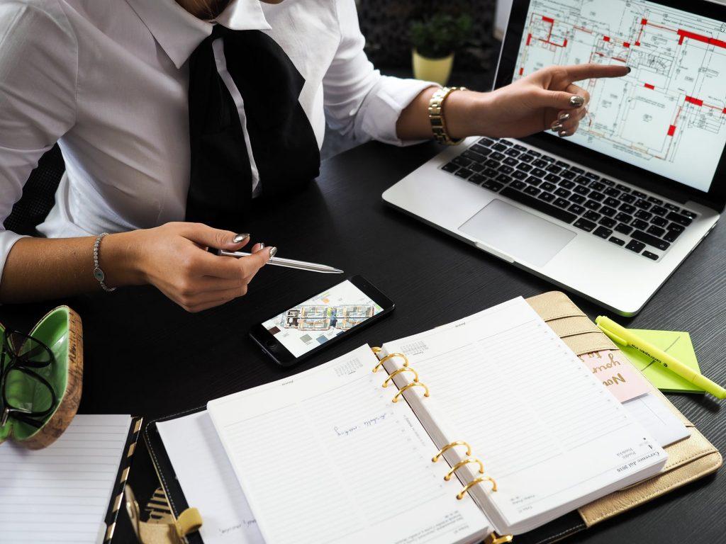 Agent immobilier qui étudie les plans d'un bien avec un acheteur