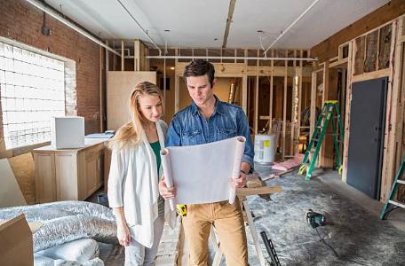un homme et une femme qui regardent des plans dans une maison en construction