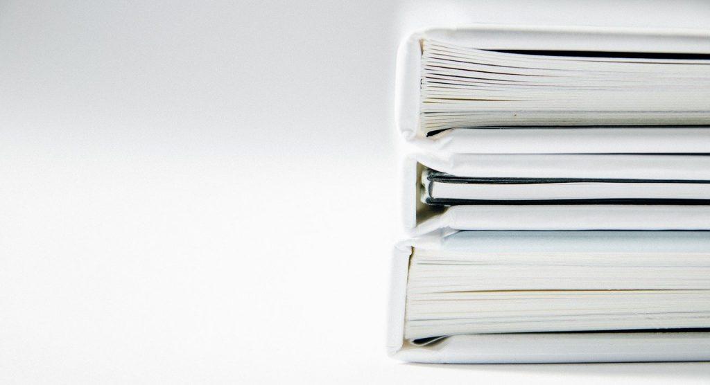 livres épais avec des couvertures blanches diposés à droite de l'image